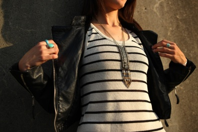 Jasmine is wearing a cascading, multi-tiered necklace made with Oxidized Hematite and Antique Brass.