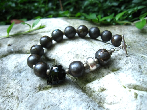 Jon's bracelet is made with Ceramic, Round Oxidized Hematite, and a Sterling Silver Barrel and Toggle, embellished with a Jet Swarovski Skull.