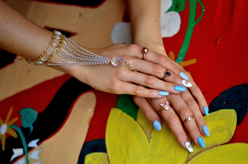 Kate's beautiful aqua-inspired nails are embellished with scales and seashells, as well as aquamarine, silver, gold, and pearl tones. Her custom Nina Spade Bracelet is made with two-toned chains and sparkling crystals.