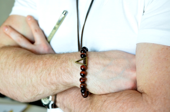 Mike's famous Pizza Bracelet is made with Tiger's Eye, Brass Findings and European Seed Beads.. a brass Trikotnik charm makes for a little slice of pizza goodness!